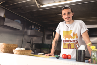 smiling-man-wearing-a-round-neck-tee-mockup-inside-his-food-truck-kitchen-a20299